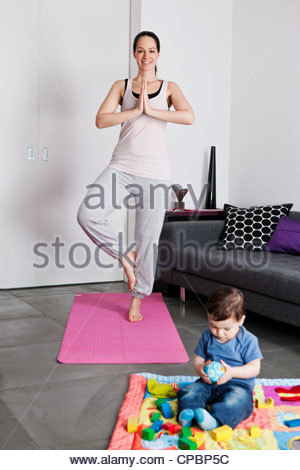 A young mother practicing yoga at home whilst her baby son plays on the floor - Stock Photo