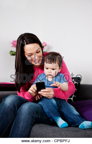 A mother and her baby son looking at a mobile phone - Stock Photo