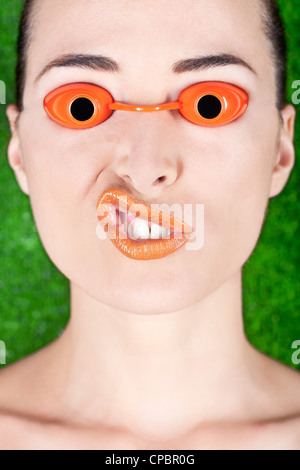 Closeup of a beautiful woman wearing tanning bed glasses and pulling a strange face isolated on green - Stock Photo