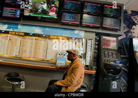 People in betting shop placing bets during grand national horse race - Stock Photo