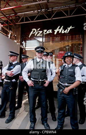 Police guarding shops on Oxford Street against Occupy London protesters and Workfare demonstrators - Stock Photo