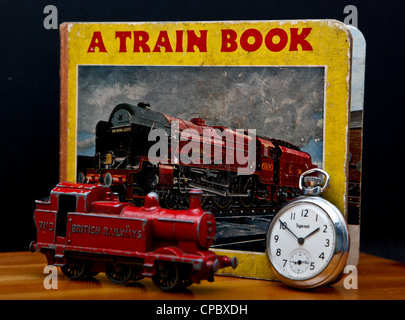 An old child's book about trains with a toy train and pocket watch in front of it. Concept of trains running on - Stock Photo