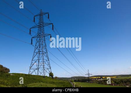 Electricity pylon against deep blue sky - Stock Photo