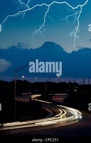 lightning bolt in night sky over highway