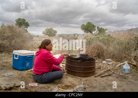 A homeless woman cooks corn on a primitive outdoor grill a primitive outdoor encampment in the desert town of Victorville, - Stock Photo