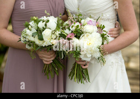 bride and bridesmaid holding floral wedding bouquets