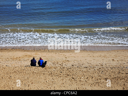 An elderly couple with their dog sitting on the beach and staring out to sea at Happisburgh, Norfolk, England, United - Stock Photo
