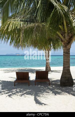 Two empty deckchairs under a palm tree on  Ko Lipeh island, Thailand - Stock Photo