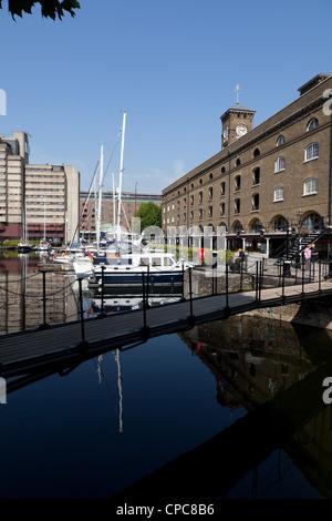 Footbridge and buildings reflected in water of St Katharine Docks marina, east London - Stock Photo