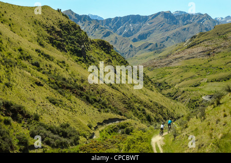 Mountain bikers descending the Pack Track, Skippers Canyon, near Queenstown, with Mt Aurum on the skyline, New Zealand - Stock Photo