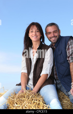 Couple sitting on haystack - Stock Photo