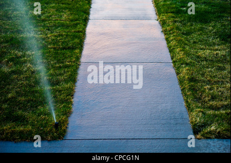Sunset colors reflect on a wet sidewalk. Automated irrigation system waters the grass lawn on the property of a - Stock Photo