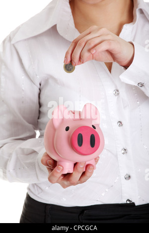 Woman putting euro coin in piggy bank. Isolated - Stock Photo