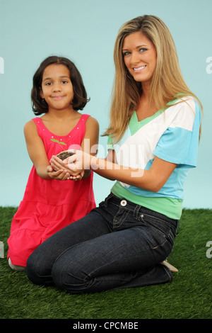 Woman and Girl Holding A New Plant In Dirt - Stock Photo