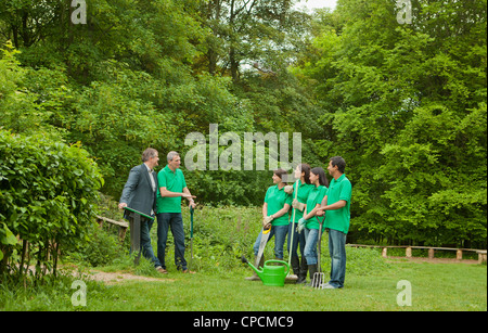 Gardeners with businessman in park - Stock Photo