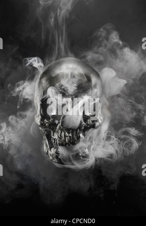 Smoke pouring from metal skull - Stock Photo