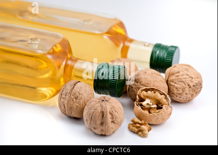 Two bottle of walnut oil and walnats on the white background - Stock Photo