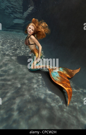 Young blond mermaid at the bottom of a pool in Virginia Beach, Virginia - Stock Photo