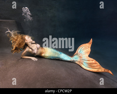 Blond mermaid laying at the bottom of a pool in Virginia Beach, Virginia. - Stock Photo