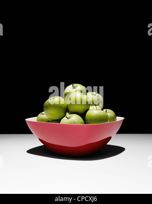 Bowl of green apples on table - Stock Photo