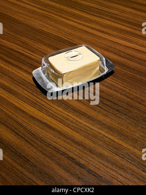 Butter in dish on wooden table - Stock Photo
