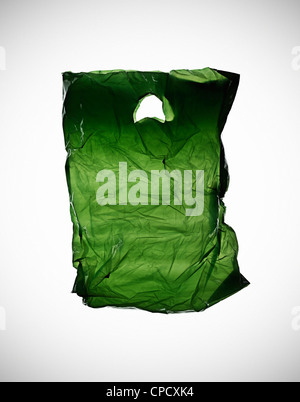 Crumpled green plastic bag on table - Stock Photo