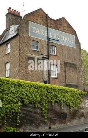 Painted 'Take Courage' beer advertisement on side of building, London, UK - Stock Photo