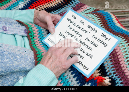 Elderly woman using a communication card pointing out she needs the bathroom(cared for in a home or at home) - Stock Photo