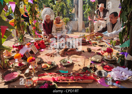 Priest with offerings at a rural Nepalese Hindu marriage ceremony, Pokhara, Nepal, Asia - Stock Photo