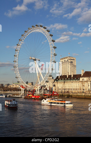 Cruise boats sail past County Hall and the London Eye on the South Bank of the River Thames, London, England, United - Stock Photo