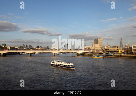 A cruise boat on River Thames, ahead of Waterloo Bridge and the skyline of the City, from Westminster, London, England, - Stock Photo