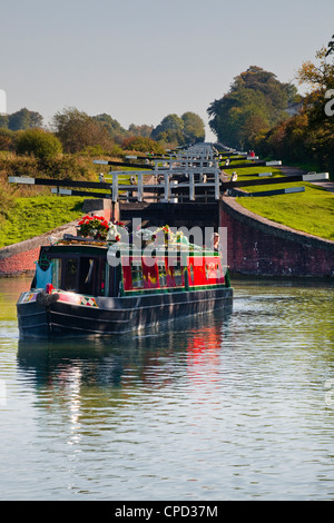 A canal boat leaving the famous series of locks at Caen Hill on the Kennet and Avon Canal, Wiltshire, England, United - Stock Photo