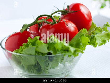 Red tomatoes in a transparent round salad bowl - Stock Photo