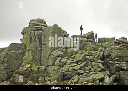 A man encourages a woman to climb up rocks to join him, Mother Cap, Peak District, Derbyshire, UK. - Stock Photo