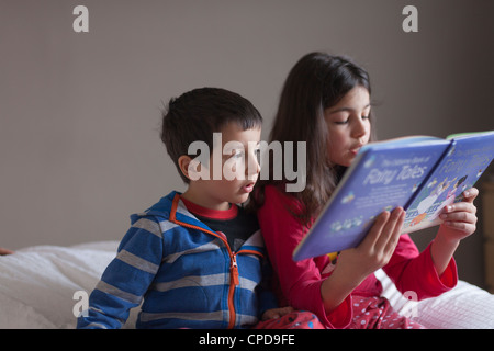 Girl reading fairy tales to her young brother. - Stock Photo
