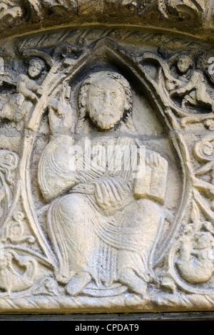 Barfrestone or Barfreston St Nicholas Church Kent uk. Figure of Christ with bible above he door to enter the church. - Stock Photo