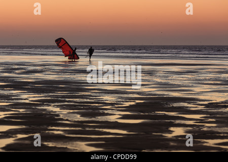 Two men on the beach at sunset walking with a kite surfer, Essaouira,  Morocco - Stock Photo