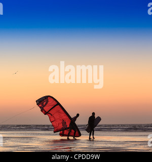 Two men on the beach at sunset walking with a kite surfer sail, Essaouira,  Morocco - Stock Photo