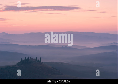 A dawn view over the misty hills of Val d'Orcia and the Belvedere, San Quirico d'Orcia, Tuscany, Italy, Europe - Stock Photo