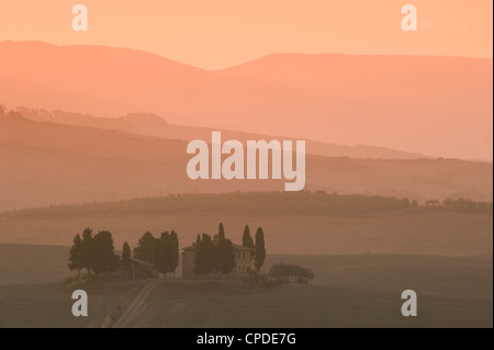 Dawn at Penella, a farmhouse surrounded by cypress trees and the misty hills of Val d'Orcia near Pienza, Tuscany, - Stock Photo