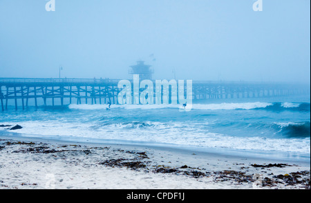 San Clemente pier with surfers on a foggy day, California, United States of America, North America - Stock Photo