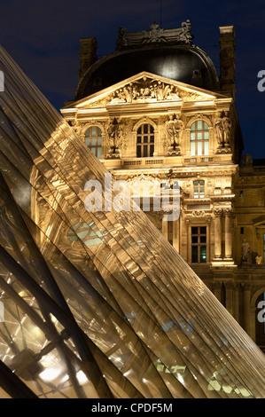 Louvre reflections in glass pyramid at twilight, Rue de Rivoli, Paris, France, Europe - Stock Photo