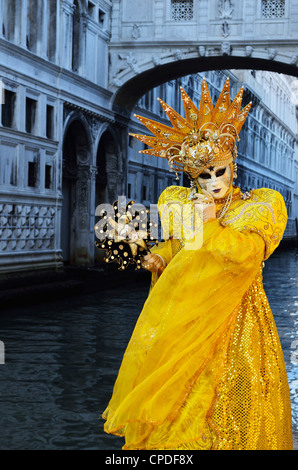 Masked figure in costume at the 2012 Carnival, with Ponte di Sospiri in the background, Venice, Veneto, Italy, Europe - Stock Photo