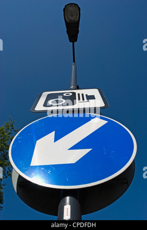 british road sign indicating traffic should keep to the left, below sign for speed limit enforcement camera - Stock Photo