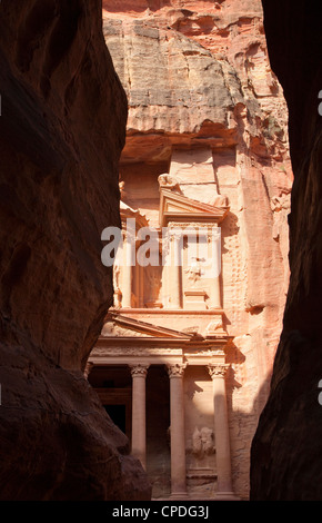 The facade of the Treasury (Al Khazneh) carved into the red rock, seen from the Siq, Petra, Jordan, Middle East - Stock Photo