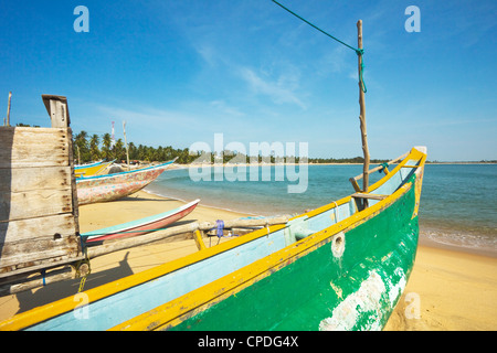 Outrigger fishing boats on this popular surf beach, badly hit by the 2004 tsunami, Arugam Bay, Eastern Province, - Stock Photo