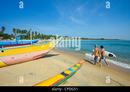 Surfers and fishing boats on this popular surf beach, badly hit by the 2004 tsunami, Arugam Bay, Eastern Province, - Stock Photo