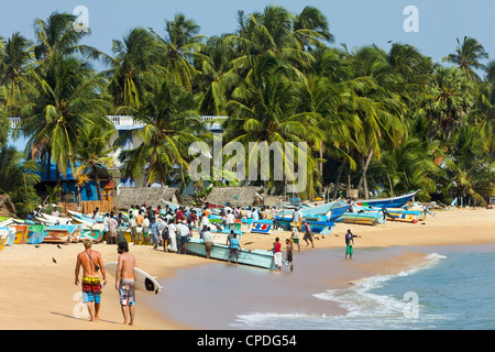 Tourists stroll whilst local fishermen work on this popular surf beach, Arugam Bay, Eastern Province, Sri Lanka, - Stock Photo