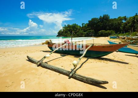 Outrigger fishing boat at this quiet south coast retreat beach, Talalla, near Matara, Southern Province, Sri Lanka, - Stock Photo