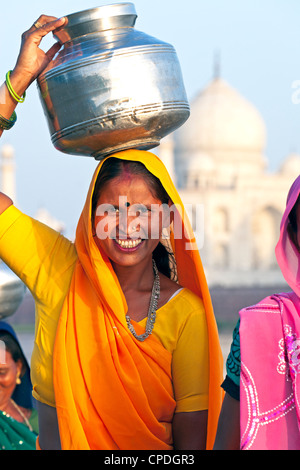 Woman carrying water pot on her head in front of the Taj Mahal, Agra, Uttar Pradesh state, India, Asia